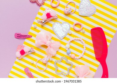 Little girl accessories lifestyle set on lilac and yellow striped background. Hair clips, hairpins, bow tie on pink background. Fashion hair accessories for little girls. Flat lay.