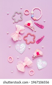 Little girl accessories lifestyle set on lilac background. Hair clips, hairpins, bow tie on pink background. Fashion hair accessories for little girls. Flat lay.