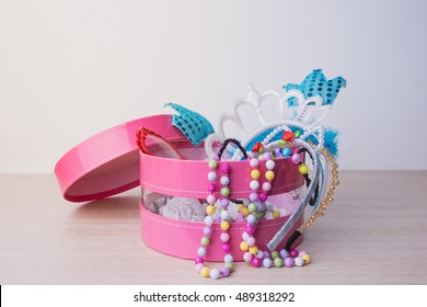 Little girl accessories lifestyle set in a pink box. Headbands, necklace,eye wear on wood table.