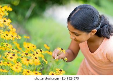 Little Girl Admiring Sunflowers in a Garden
