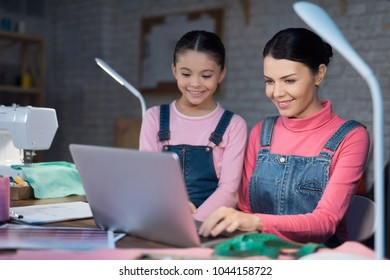 A little girl and an adult woman are looking at something on the laptop. They are with mom in the sewing workshop.