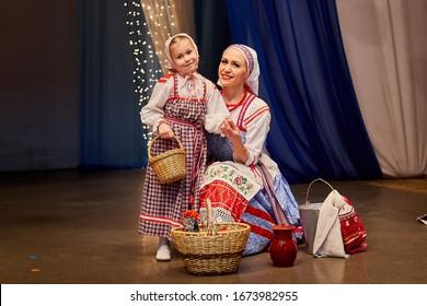 Kleines Mädchen und eine erwachsene Frau in russischem Nationalkleid posieren während des Fotoshootings auf der Bühne. Mutter und Tochter zusammen