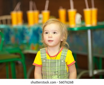 Little girl against table with yellow glasses in children's cafe.