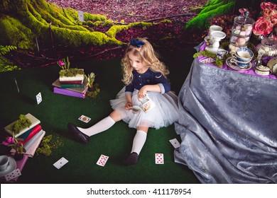 Little girl as Alice in Wonderland pouring tea