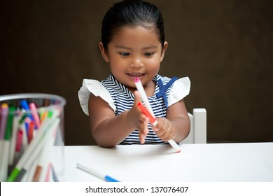 Little girl amazed and playing with colorful markers on a white table
