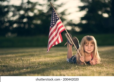 Little girl with American flag laying on the grass.