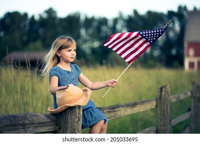 Little girl with American flag sitting on the fence.