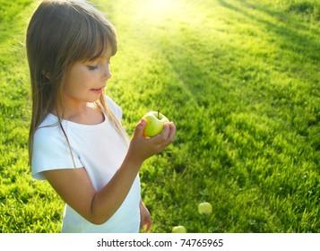 Little girl with apple in the garden