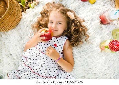 little girl with apple resting and eating in park on picnic. Happiness summer weekend concept.