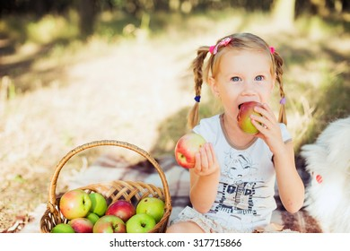 little girl with apples in park