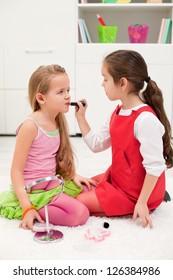 Little girl applying lipstick on her girlfriend's mouth
