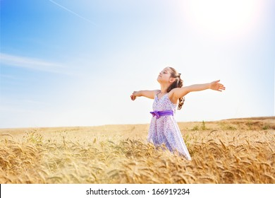 Little girl with arms outstretched in a wheat field,copy space.Flare light