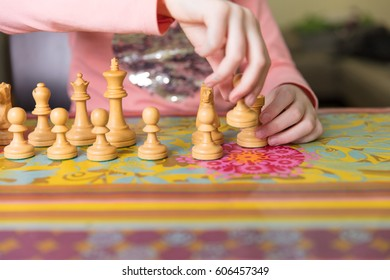 Little girl arranging chess figures before playing the game at home.