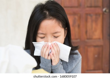 little girl asian catches a cold when season change, wiping nose with tissue. sick kid blowing nose into tissue, Unhealthy child suffering from running nose or sneezing and covering his nose mouth.