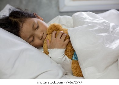little girl Asian girl sleeps in bed with a toy teddy bear.Sick or Sad child preschool age in bed on white background