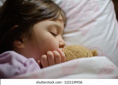 Little girl asleep with her teddy bear.