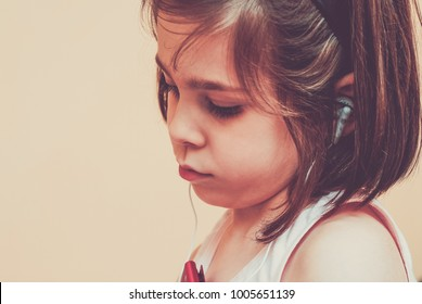 Little girl with Asperger's syndrome listens to audio tracks from her digital audio player