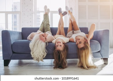 Little girl, attractive young mother and charming grandmother are having fun and lying on sofa while spending time together at home. Women's generation. International Women's Day. Happy Mother's Day.