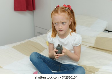 little girl with autism and sensory needs playing with stress ball toy whilst sitting on bed.