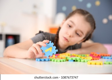 Little girl with autistic disorder playing at home, closeup of puzzles