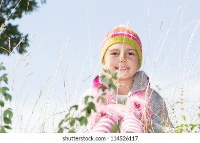 Little girl in autumn clothes sitting on the grass outdoor