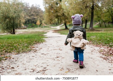 Little girl in autumn forest with teddy bear backpack. Fall day. Little girl exploring nature.
