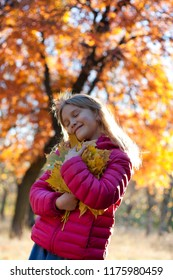 A little girl in an autumn park holds a bouquet of yellow leaves in her hands. Smiles happily, squinting in the sun