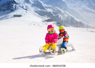 Little girl and baby boy play with snow on a sleigh ride in Swiss Alps mountains. Children sledding on sunny and snowy winter day. Toddler kids riding a sledge in mountain landscape of Switzerland.