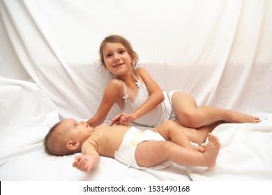 Little girl and baby. Concept of happy family, sisterhood, childhood, lifestyle, motherhood, parenthood.