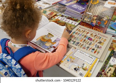little girl back view flips through a children's storybook at book fair Turin Italy circa May 2017