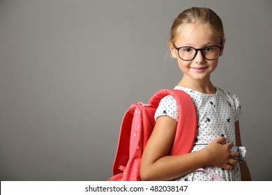 Little girl with backpack over one shoulder