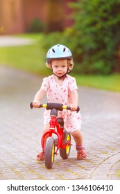 little girl with balance bike and  helmet smiling