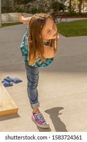 A little girl balances herself on one leg as she just finished tossing a bean bag.  The casually dressed girl-focused in the sunlight enjoys playing cornhole games on the sidewalk at the park.