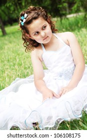 Little girl in ball dress sitting on the green meadow