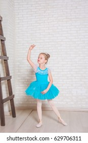 The little girl as ballerina dance with ladder on wooden floor. dreams of becoming a ballerina. Child girl in a blue tutu studying ballet. Pointe shoes for ballet