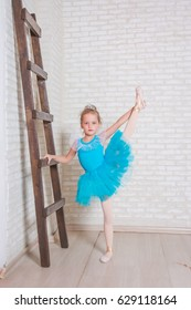The little girl as ballerina dance on wooden floor. dreams of becoming a ballerina. Child girl in a blue tutu studying ballet. Amazing twine .showing the twine while,flexibility