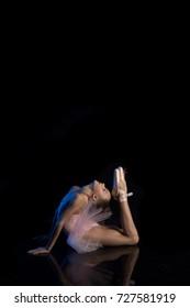 Little girl ballerina posing against a black background in a blue scenic light