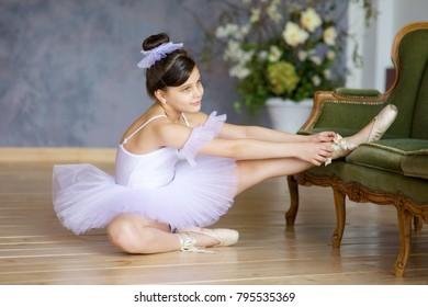 Little girl ballerina in white tutu sitting on floor in ballet class.