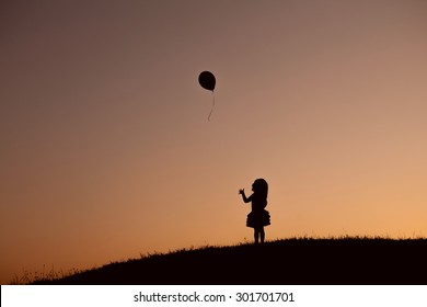 little girl with balloon in the park at sunset