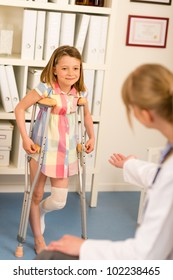 Little girl with bandaged leg standing with crutches surgery office