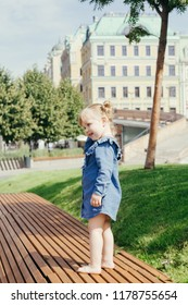 Little girl barefoot walking in a city park on a warm sunny day