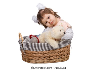 The little girl in a basket with toys