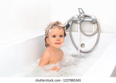 A little girl bathing in the bathroom with foam. Adorable baby girl with soap suds on hair taking bath. Closeup portrait of smiling kid, health care and hygiene concept. Isolated on white background.