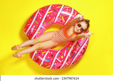 Little girl in a bathing suit and glasses, lying on a donut inflatable circle. A child shows thumbs up. Yellow background Top view. Summer concept.