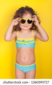 Little girl in a bathing suit and sunglasses on a yellow background