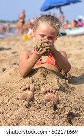 a little girl at the beach playing with sand