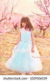 Little girl in beautiful blue dress in spring garden