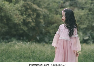 Little girl in a beautiful dress in a garden at sunset in Hanoi, Vietnam.
