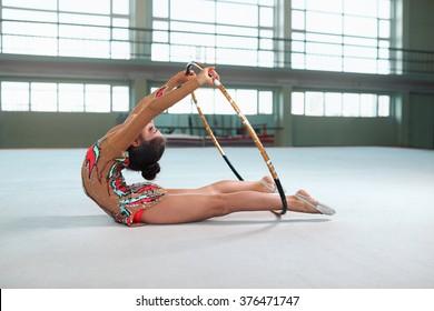 Little girl in beautiful gymnastic dress doing exercise with hoop on floor