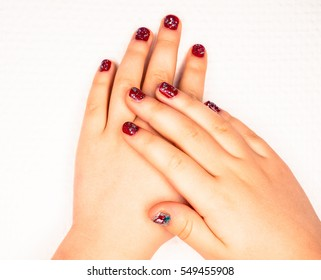 Little girl with beautiful manicure in dark pink, towards white paper